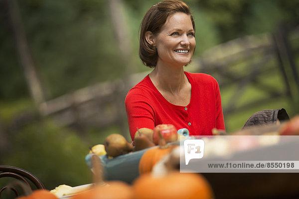 Eine Frau im roten Hemd  an einem Erntetisch im Freien.