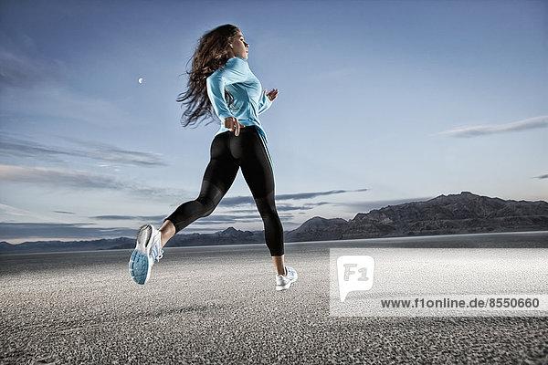 Eine junge Frau läuft durch die Landschaft auf der Salzfläche in der Nähe der Stadt Salt Lake City.