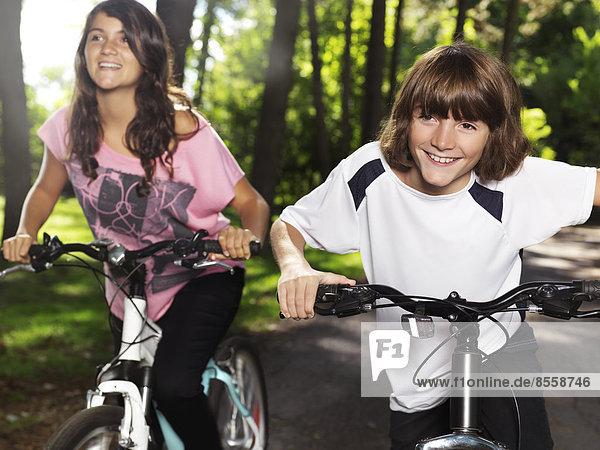 Zwei glückliche Kinder  ein Junge und ein Mädchen  auf Fahrrädern