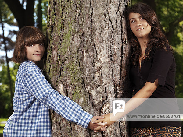 Brother and sister  10 and 13  holding hands around a tree