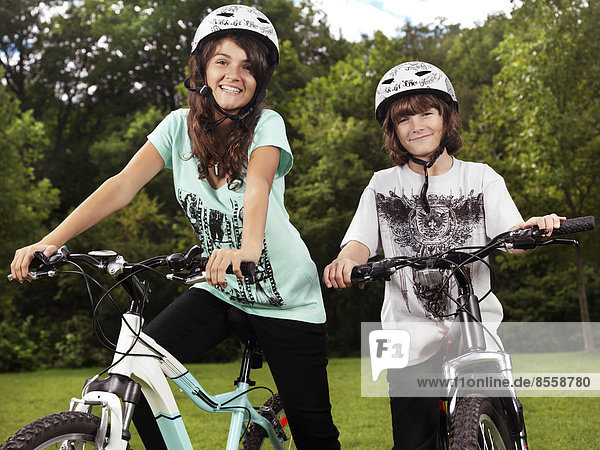 Zwei glückliche Kinder  ein Junge und ein Mädchen  auf Fahrrädern mit Helmen