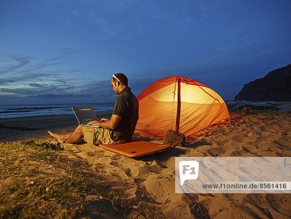 Mann mit Laptop sitzt in der Dämmerung vor Zelt am Sandstrand der Napali Coast  Polihale State Park  Kaua'i  Hawaii  USA Mann mit Laptop sitzt in der Dämmerung vor Zelt am Sandstrand der Napali Coast, Polihale State Park, Kaua'i, Hawaii, USA