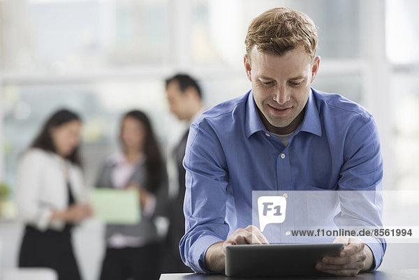 Junge Berufstätige bei der Arbeit. Ein Mann in einem Hemd mit offenem Hals  der ein digitales Tablet benutzt. Eine Gruppe von Männern und Frauen im Hintergrund.