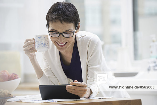 An office or apartment interior in New York City. A woman dressed for work in cream jacket  holding a cup of coffee. Checking her digital tablet.