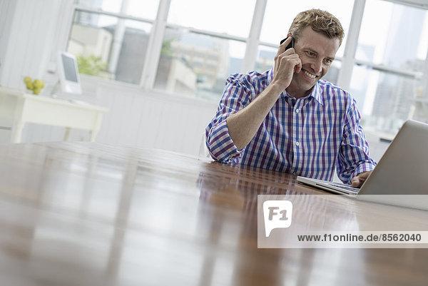 Eine Büro- oder Wohnungseinrichtung in New York City. Ein Mann benutzt das Telefon und tippt auf seinem Laptop.