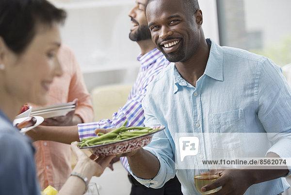 Ein Großraumbüro in New York City. Ein Arbeitsessen  ein Salatbuffet. Eine Gruppe von Männern und Frauen gemischten Alters und unterschiedlicher ethnischer Herkunft  die zusammenkommen.