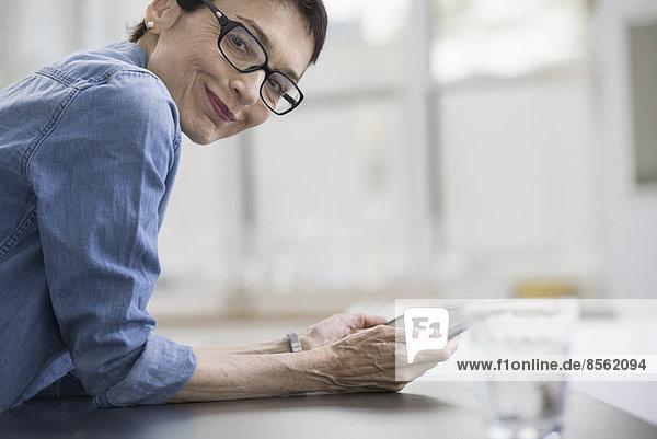 Fachleute im Büro. Ein heller und luftiger Arbeitsplatz. Eine reife Frau in einem blauen Jeanshemd  die ein digitales Tablet hält.