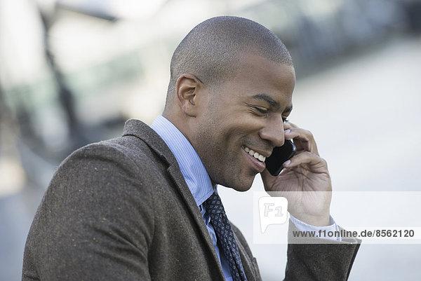 Geschäftsleute in der Stadt. Unterwegs in Kontakt bleiben. Ein Mann sitzt auf einer Bank und telefoniert mit seinem Smartphone.