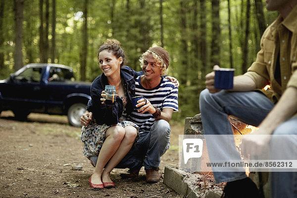 Ein Campingplatz in den Wäldern. Drei Personen sitzen in der Abenddämmerung um ein Lagerfeuer herum.