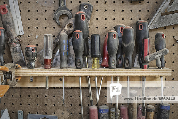 Eine zurückgewonnene Holzwerkstatt. Eine Werkzeugtafel mit Schlitzen für Schraubendreher und handgehaltene Holzbearbeitungswerkzeuge.