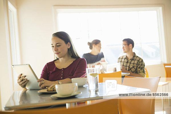 Eine Frau in einem Café  die mit einem Tablet-Computer liest.