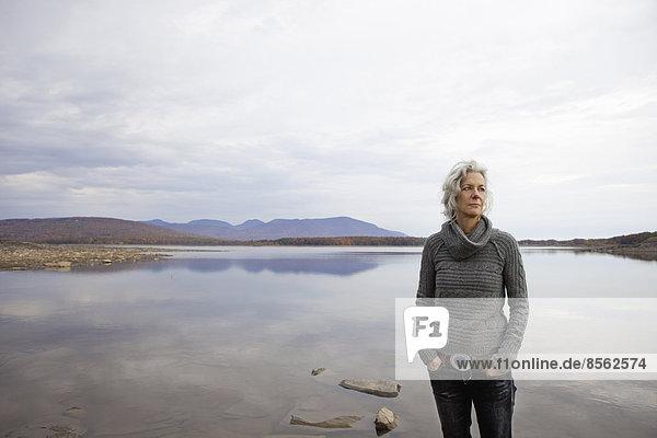 Eine Frau  die am Ufer eines ruhigen Sees über das Wasser schaut.