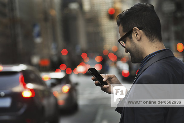A man in a dark jacket checking his cell phone  standing on a busy street at dusk.