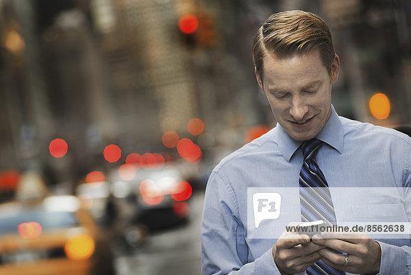 Ein Mann in einem Anzug  der sein Mobiltelefon überprüft  steht in der Abenddämmerung auf einem Bürgersteig der Stadt.