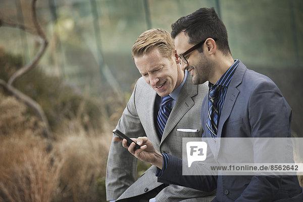 Zwei Männer in formeller Geschäftskleidung  die Seite an Seite stehen und auf einen Handybildschirm oder ein Mobiltelefon schauen.