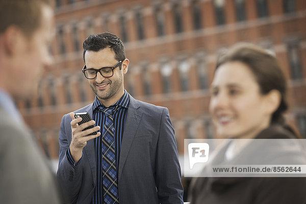 Drei Personen  zwei im Vordergrund  und ein Mann  der auf das Display eines Mobiltelefons schaut.