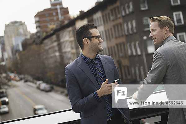 Zwei Männer stehen sprechend auf einem erhöhten Gehweg über einer Stadtstraße.