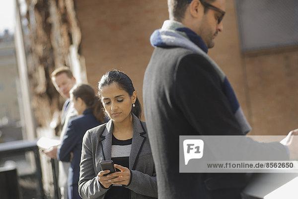 Zwei Frauen und zwei Männer auf dem Bürgersteig. Zwei Personen überprüfen ihre Mobiltelefone.