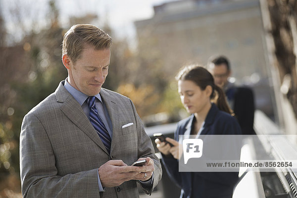Drei Personen  die in der Stadt auf dem Bürgersteig stehen und ihre Telefone überprüfen. Zwei Männer und eine Frau.
