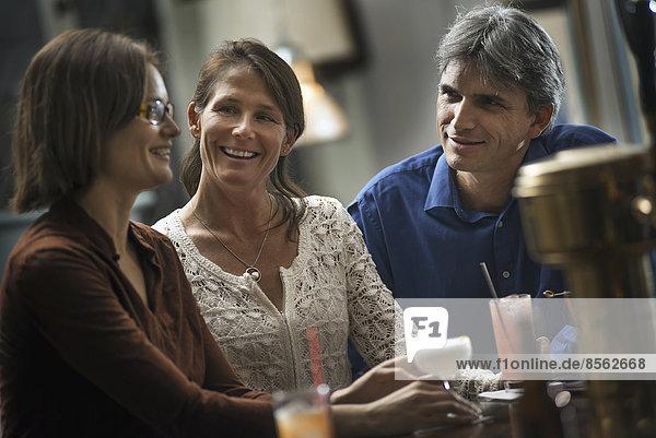 Drei Personen treffen sich auf einen Drink. Zwei Frauen und ein Mann sitzen an einer Bar. Freunde treffen sich zum geselligen Beisammensein.