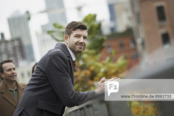 Stadtleben. Ein Mann im Wintermantel  der sich an ein Geländer lehnt und sich eine Auszeit nimmt. Stadtlandschaft mit Gebäuden.