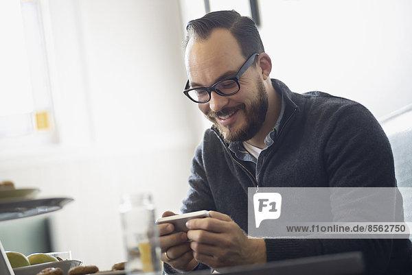 Eine Person  die an einem Tisch in einem Coffeeshop sitzt. Ein bärtiger Mann trinkt einen Kaffee.