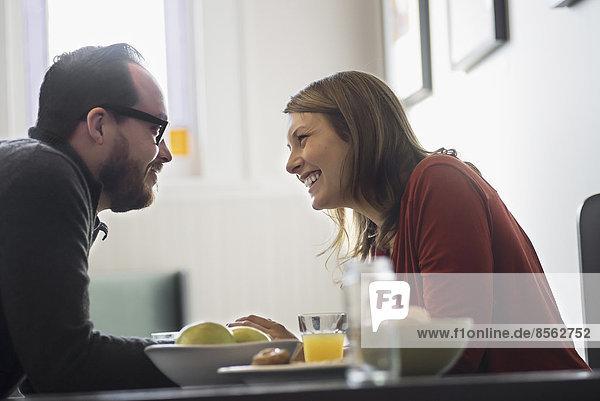 Ein Ehepaar sitzt beim Frühstück in einem Coffeeshop. Sie lehnen sich zueinander.