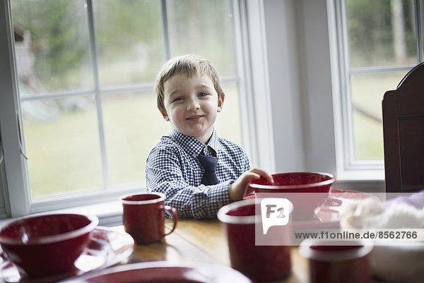 Ein Kind  das in einer Familie zu Hause am Tisch sitzt. Ein Tisch  der für eine Mahlzeit gedeckt wurde.