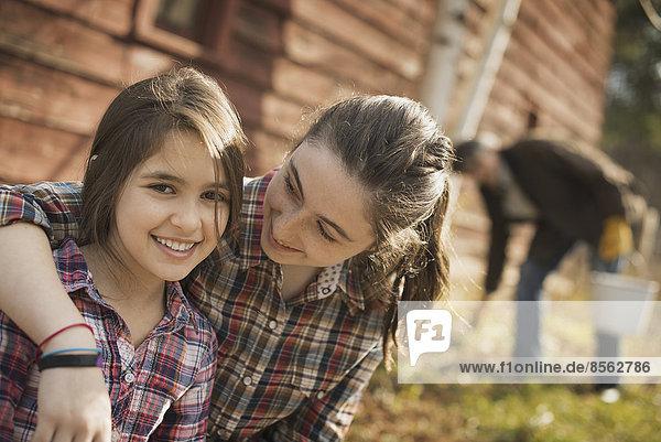 Zwei Mädchen und ein Mann vor einer Scheune auf einem Biohof.