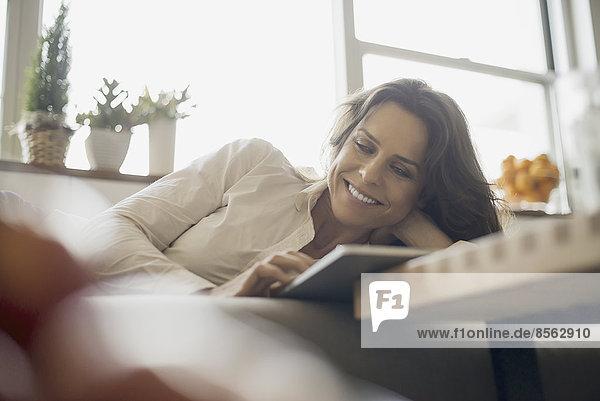 Frau zu Hause mit elektronischem Tablett