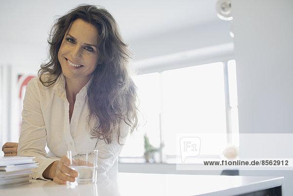 Frau zu Hause in der Küche mit einem Glas Wasser