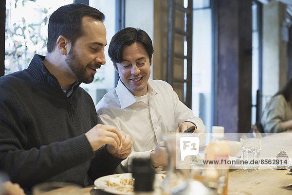 Männer  die am Restauranttisch Texte austauschen