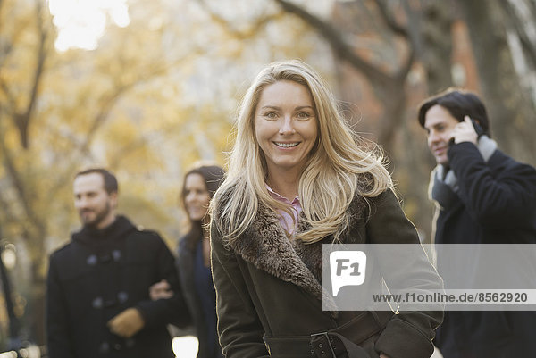 Erwachsenengruppe im Stadtpark  Frau davor