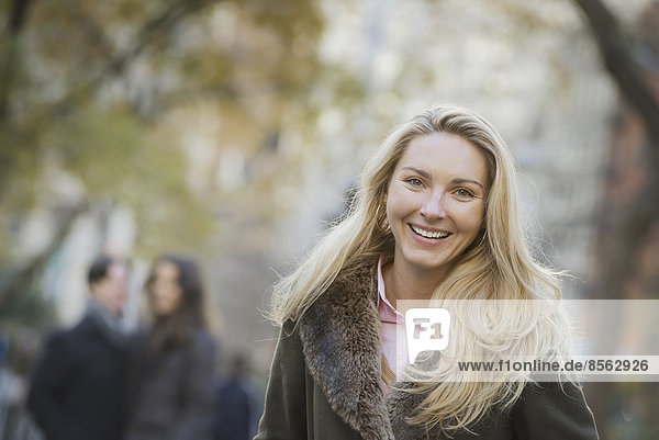 Group walking in urban park,  woman in front