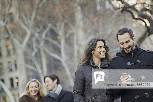 Paar  das mit einem Smartphone im Stadtpark spazieren geht