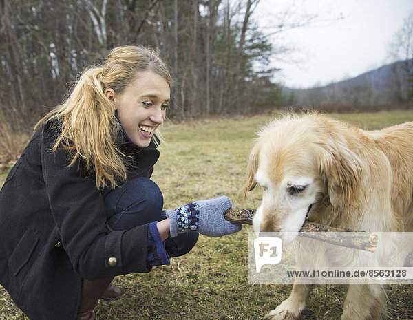 Außenaufnahme junge Frau junge Frauen Winter gehen Hund Golden Retriever freie Natur