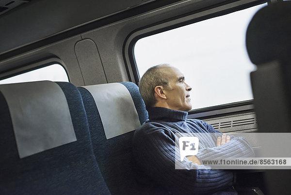 Ein reifer Mann  der auf einer Zugfahrt am Fenster sitzt und in die Ferne schaut.