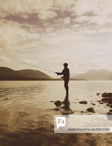 Silhouette eines Mannes beim Fliegenfischen in ruhigen Gewässern am Waschusett-Inlet im Glacier-Bay-Nationalpark in Alaska.