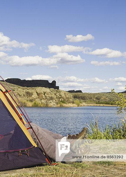 Ein kleines Zelt  das an den Ufern der Sun Lakes im Sun Lakes State Park aufgestellt wurde. Die Füße eines Mannes in Slippern ragen heraus.