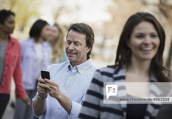 Menschen im Frühling in der Stadt im Freien. Ein Mann unter einer Gruppe von Männern und Frauen  der sein Handy überprüft.