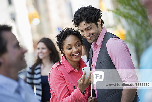 People outdoors in the city in spring time. New York City park. Four people,  men and women. A couple looking at a mobile phone screen.