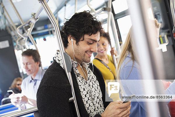 New Yorker Stadtpark. Menschen  Männer und Frauen in einem Stadtbus. Öffentliche Verkehrsmittel. In Kontakt bleiben. Ein junger Mann  der sein Mobiltelefon überprüft.