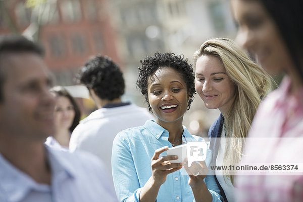 People outdoors in the city in spring time. New York City. A group of men and women  two women looking at a cell phone.