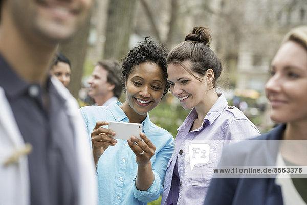 Handy Außenaufnahme Frau Mensch zwei Personen Freundschaft sehen Menschen lächeln Menschengruppe Menschengruppen Gruppe Gruppen Großstadt Zeit 2 freie Natur