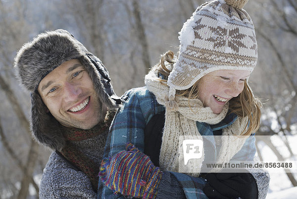 Winter scenery with snow on the ground. A young girl with a bobble hat and scarf and a man hugging her.