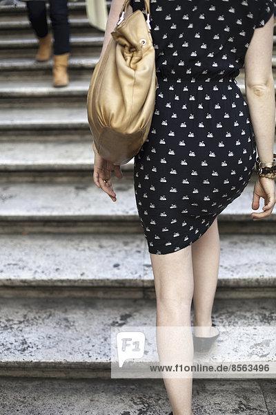 Rückenansicht einer jungen Frau  die ein blau-weiß gemustertes Kleid und eine große Handtasche trägt. Aufstieg über Marmortreppen in Rom.