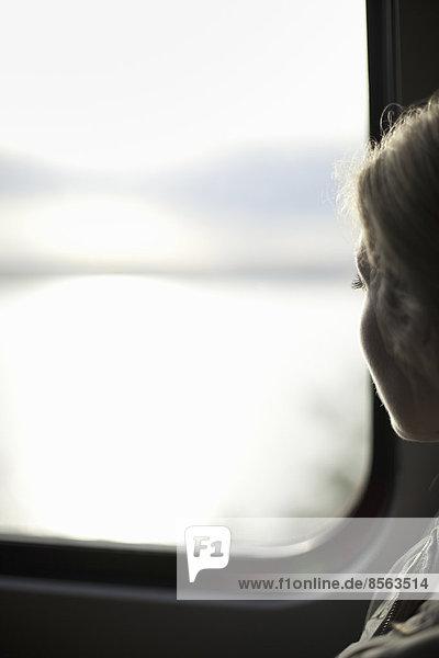 Eine Frau sitzt an einem Zugfenster und schaut auf die Aussicht.