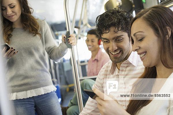 Urbaner Lebensstil. Eine Gruppe von Menschen  Männer und Frauen  in einem Stadtbus in New York City. Ein Mann mit Kopfhörern und ein Paar  das sich ein Mobiltelefon ansieht.