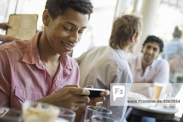 Urban Lifestyle. Three young men in a cafe. One checking his smart phone. Two talking at a table.