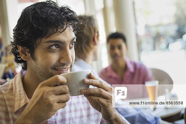 Urbaner Lebensstil. Drei junge Männer um einen Tisch in einem Cafe. Ein Mann nimmt einen Drink aus einer Tasse Kaffee.